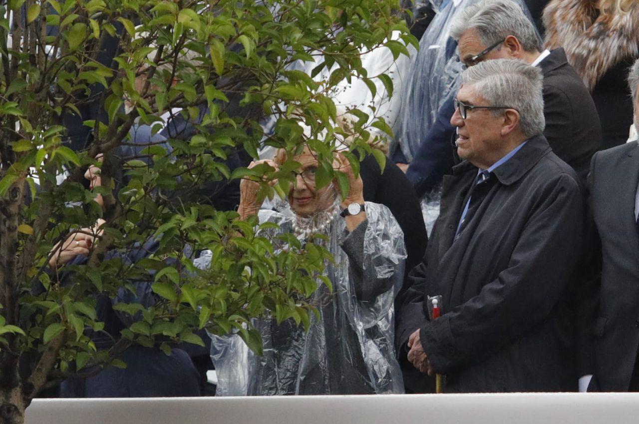 Manuela Carmena, en la tribuna de personalidades, protegiéndose de la lluvia.