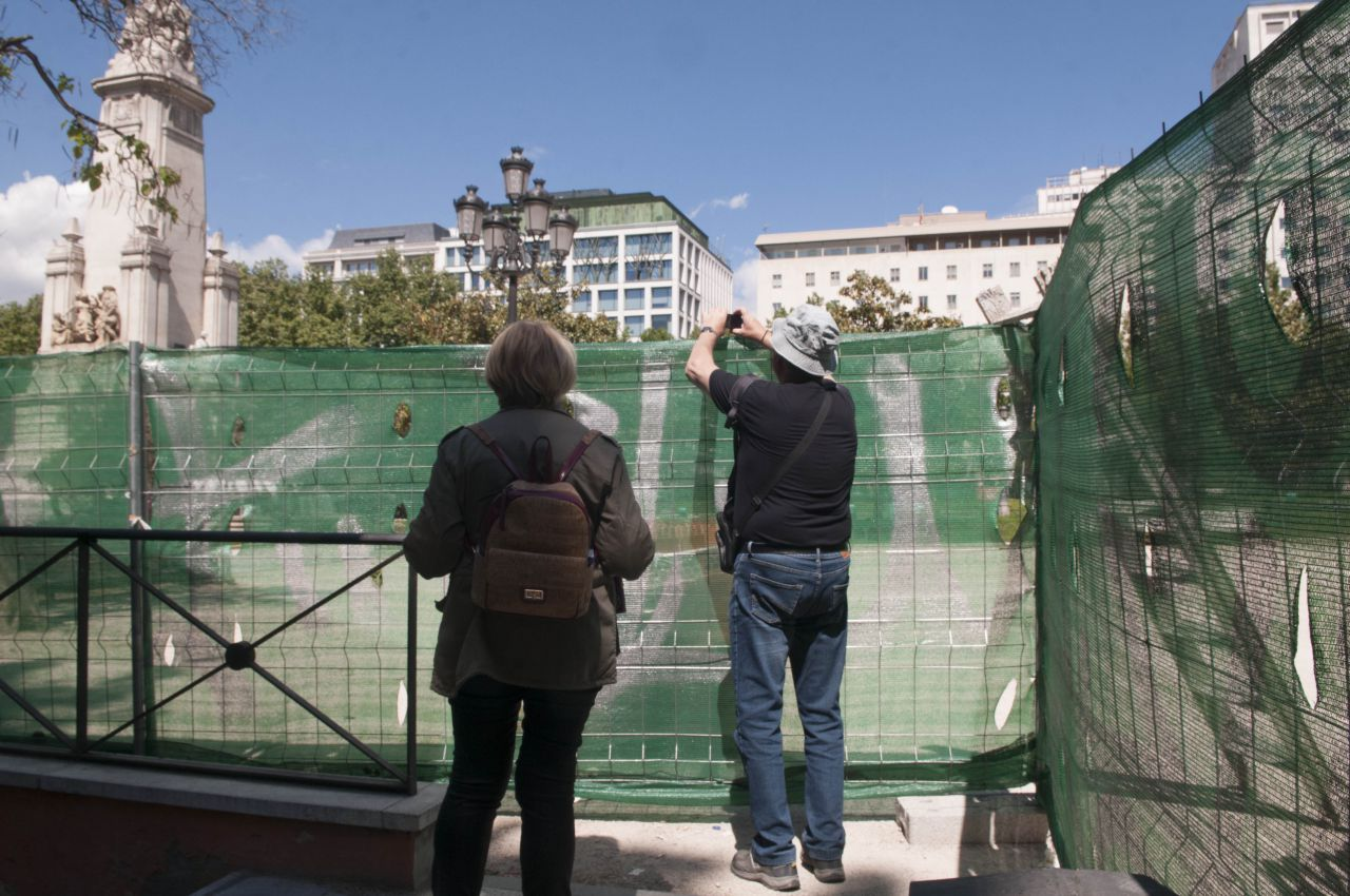 Los turistas intentan fotografiar la Plaza de España, aunque sea por encima de las vallas.