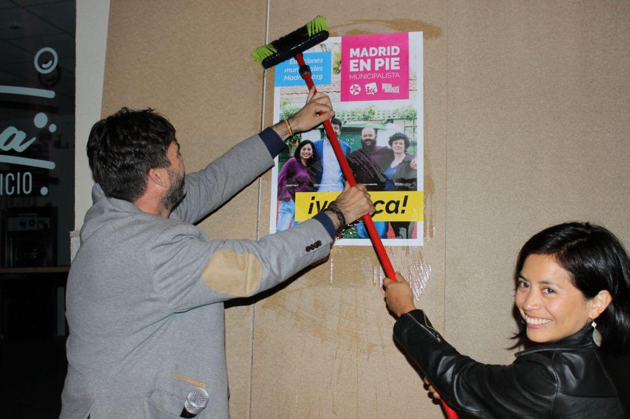 Carlos Sánchez Mato y Rommy Arce pegando uno de los carteles.