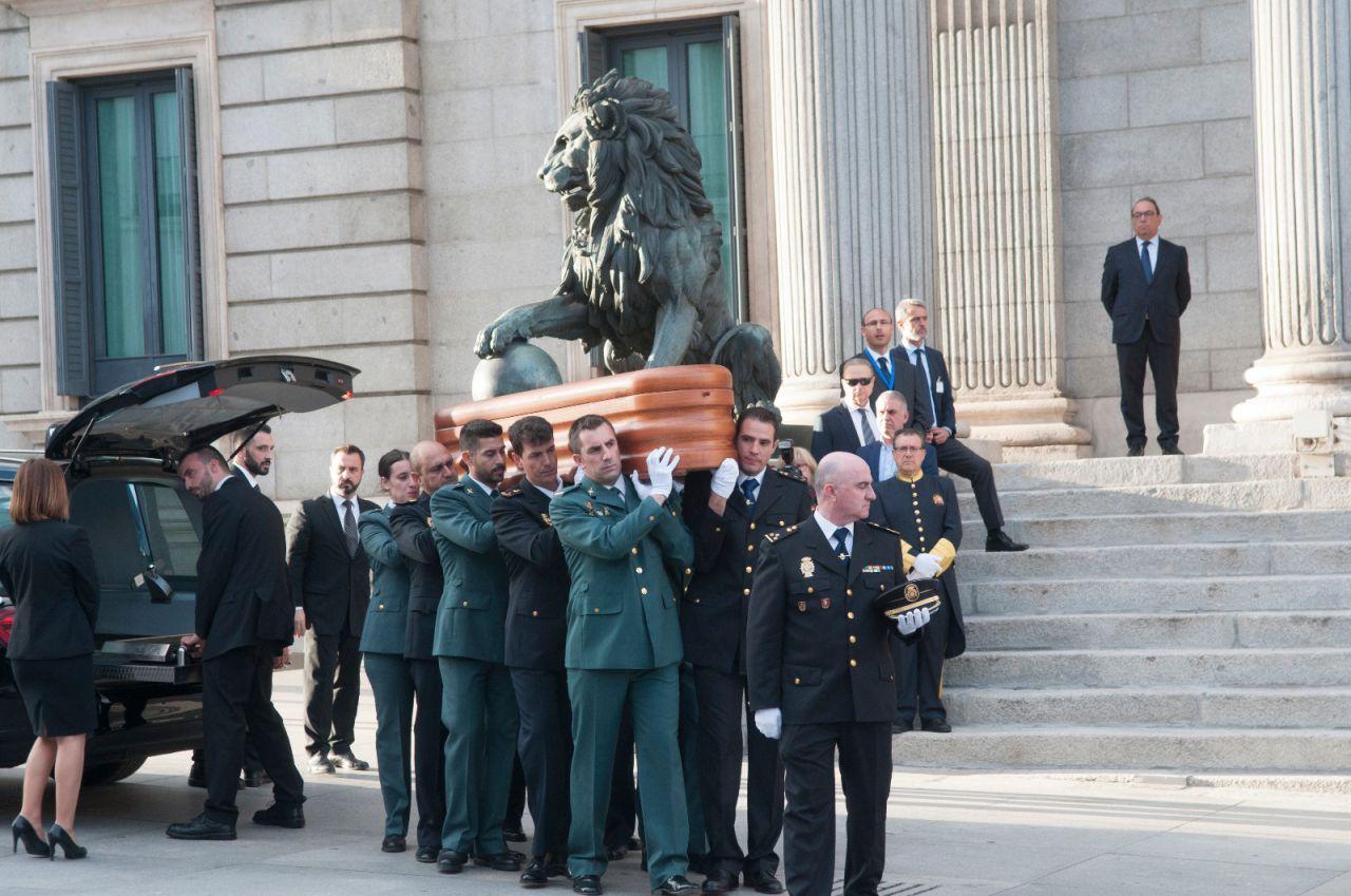 Miembros de la Guardia Civil y la Policía cargan a hombros el féretro del exministro del Interior.