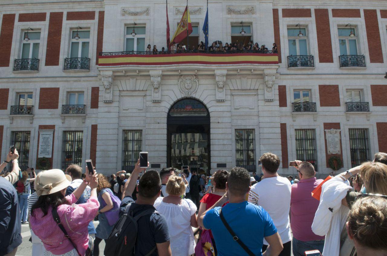 Asistentes a la Puerta del Sol observan la copa ofrecida por las jugadoras del Atlético de Madrid femenino