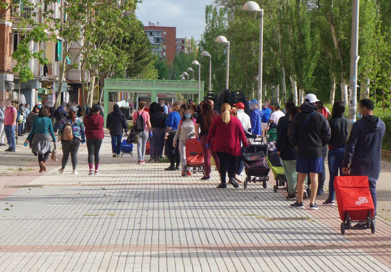 Centenares de personas hacen cola cada fin de semana para recoger alimentos en un local de Asociación de Vecinos de Aluche.