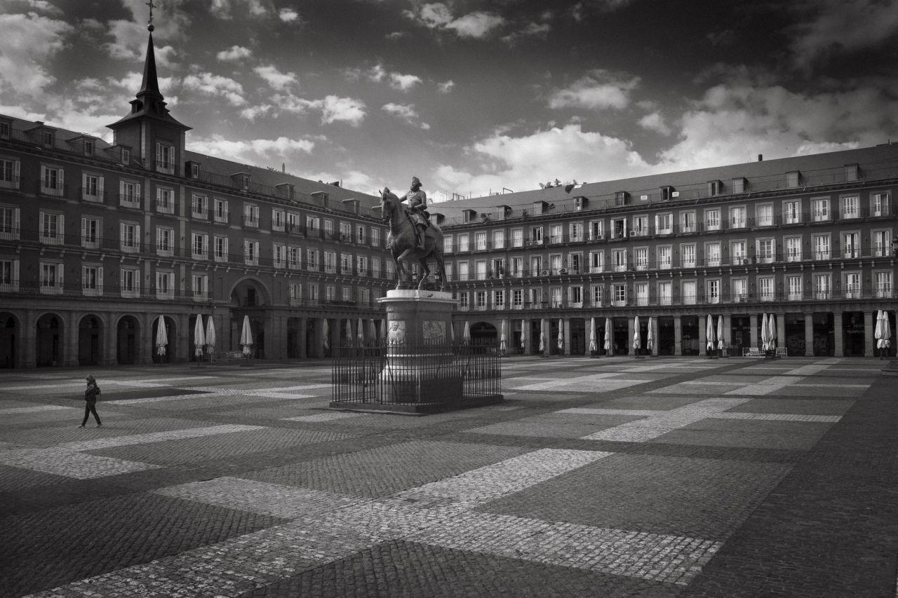 Una persona cruza la solitaria Plaza Mayor de Madrid el primer día del confinamiento. Las sombrillas recogidas son el único recuerdo de las bulliciosas terrazas.