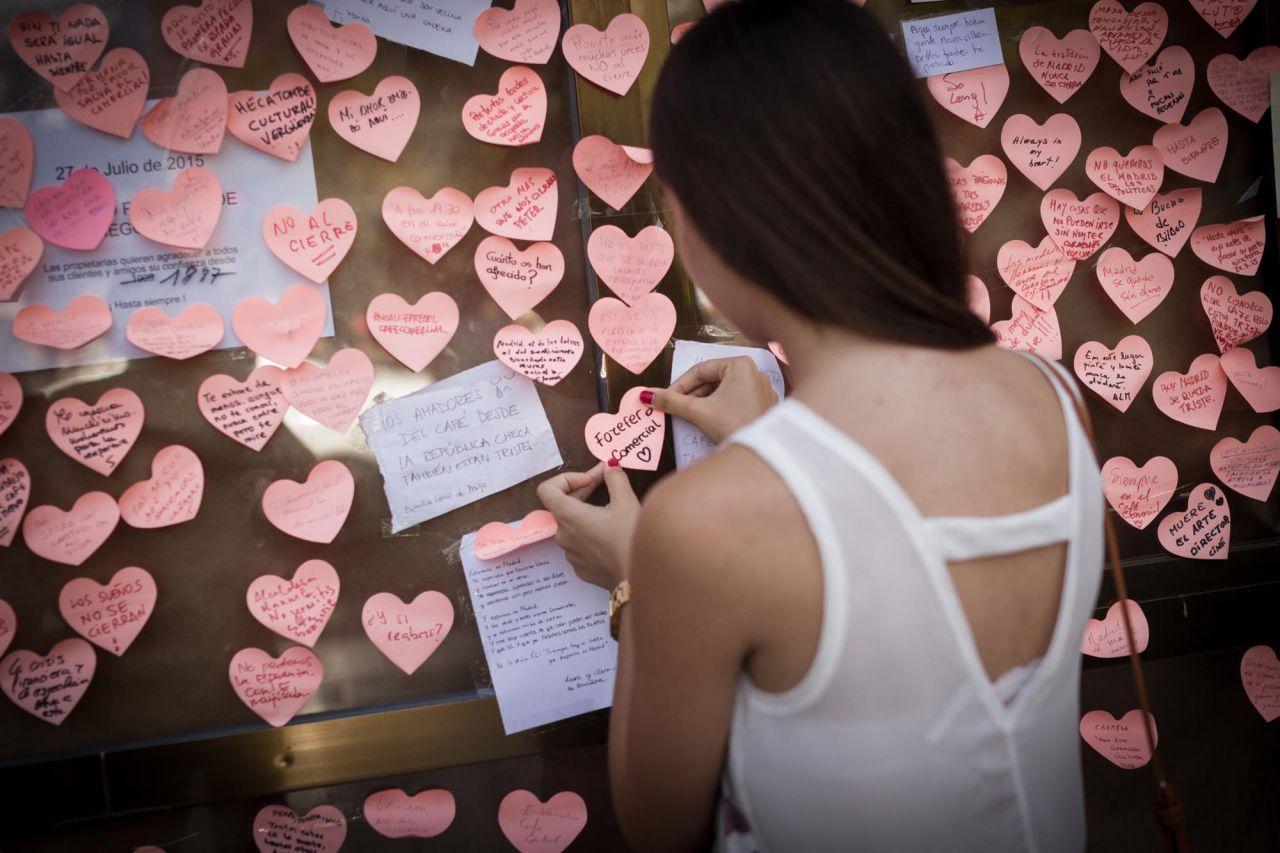 Una mujer pega un corazón de papel en uno de los escaparates del Café Comercial con el lema