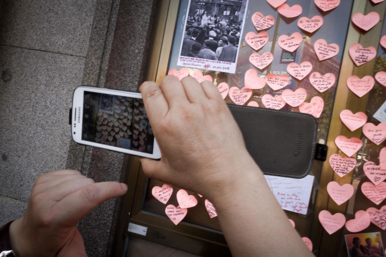 Muchas personas se acercan y hacen fotos a los recuerdos y reinvindicaciones pegados en los escaparates del Café Comercial.