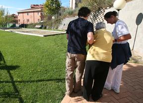 Dos personas ayudan a una anciana