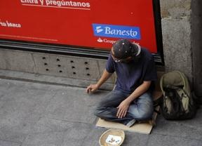 Un hombre mendiga en la puerta de un banco