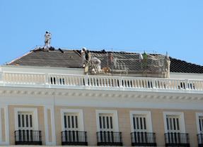 Sobre los tejados de los edificios los obreros desmontan el cartelon luminoso de Firestone tras Escuelas Aguirre  y montan en el de Sol el de Apple