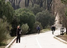 Paseantes y ciclistas disfrutan de un día soleado en la Casa de Campo.