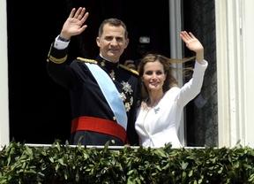 Felipe VI  y la reina Letizia saludan desde el balcón del Palacio Real en el día de la Proclamacion.