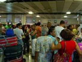 Largas colas de pasajeros en Barajas en el segundo día de la operación salida