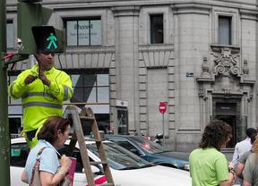 Un trabajador arregla un semáforo en la Gran Vía