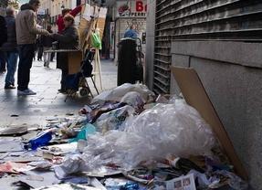 Montón de basura junto a una vendedora de lotería de navidad en la calle del Carmen por la huelga de limpieza
