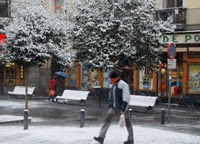 Un paseante bajo la nieve en la plaza de Pontejos