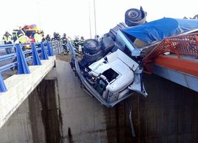 Un conductor queda atrapado en la cabina de su trailer colgando de un puente