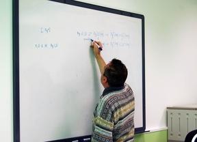 Un profesor escribe ecuaciones en la pizarra de un colegio público