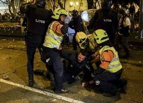 Sanitarios del Samur atienden al agente herido, protegidos por los antidisturbios.