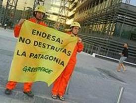 Cuatro activistas de Greenpeace decuelgan una pancarta en la sede de Endesa