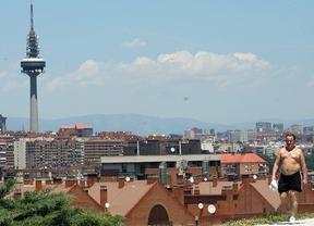 Un hombre pasea semidesnudo por el calor, con una vista de Madrid detrás