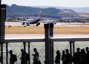 pasajeros aeropuerto Barajas en un finger para embarcar y al fondo la pista