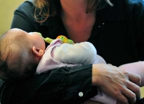Un bebé duerme en brazos de su madre