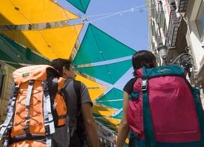 Turistas mochileros de compras por la calle Preciados.
