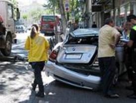 Una grúa arrastra a un coche, con su conductora, hasta empotrarlo a una farmacia