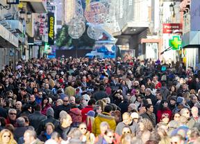 Gente en multitud va de compras navideñas por calle Preciados