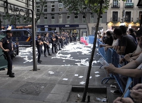 Policías y manifestantes en una protesta ante la sede del PP
