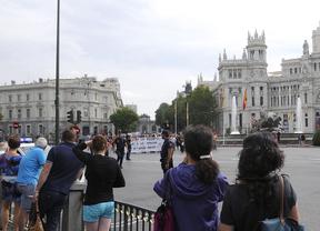 Un grupo de turistas fotografía una manifestación en Cibeles