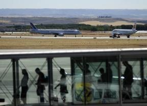 Una fila de viajeros en un finger a la espera de abordar su avión en el aeropuerto de Madrid-Barajas, al fondo aviones en la pista.