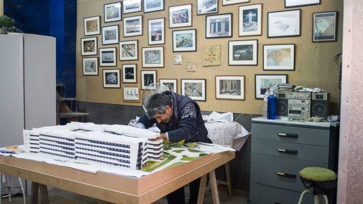 Ricardo trabaja en una maqueta delante de las fotrografías de las maquetas que ha construido.