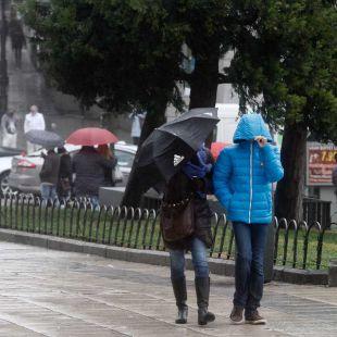 Los madrile�os se protegen del viento y lluvia