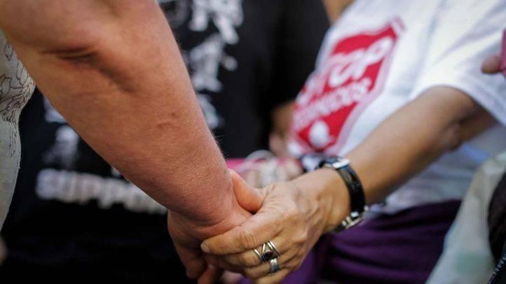 Una activista de la PAH coge la mano de Asunción en señal de cariño tras aplazar su desahucio (archivo).