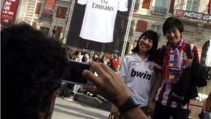 Una pareja de turistas chinos con camisetas del Real Madrid y del Atleti (Archivo)
