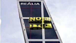 Greenpeace protesta contra el TTIP con una gran pancarta en las torres Kio