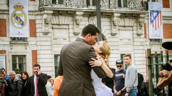 Una pareja de novios se besan después de bailar una ranchera en la Puerta del Sol.