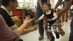 Álvaro, de cinco años y afectado por atrofia muscular espinal, camina hacia sus padres durante una prueba del exoesqueleto.