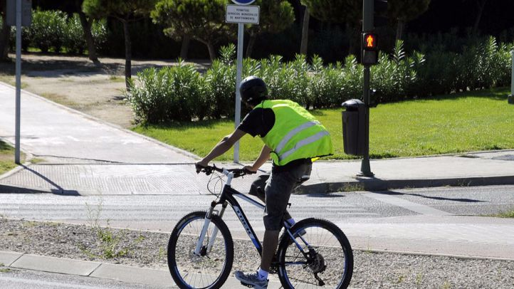 un ciclista con casco y chaleco por una calle cercana al Estadio Olimpico
