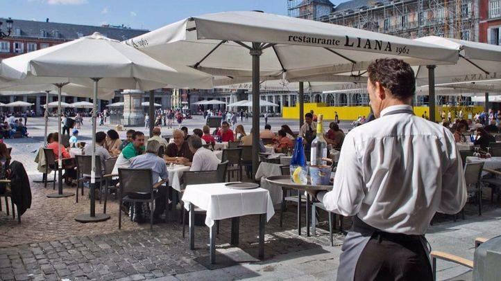 Un camarero atiende a varios turistas en una terraza de la plaza Mayor. (Archivo)
