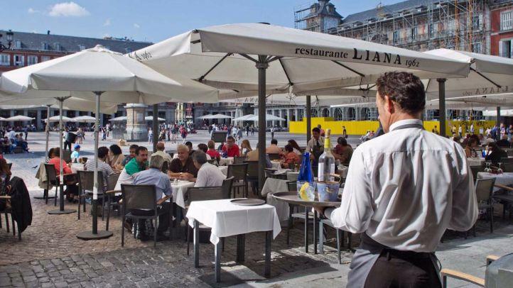Empleo libro turismo. Un camarero atiende a varios turistas en una terraza de la plaza Mayor.