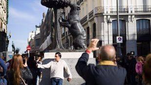 Turistas fotografi�ndose junto a la estatua del oso y el madro�o, en la Puerta del Sol.