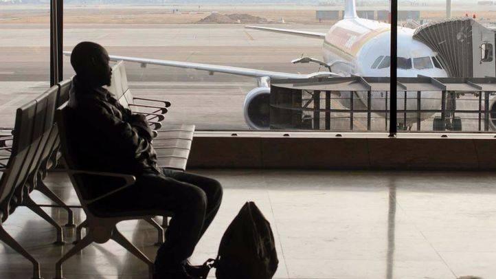 Hombre en la sala de espera sentado, esperando que salga su vuelo con un avión de fondo