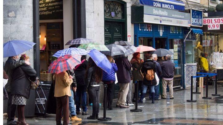 Cola bajo la lluvia frente a Doña Manolita para comprar lotería de Navidad.