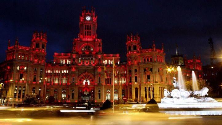 El palacio de Cibeles ha encendido su iluminación roja en homenaje al Dia Internacional del Sida.
