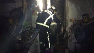 Un bombero accede al interior de la casa que ha salido ardiendo
