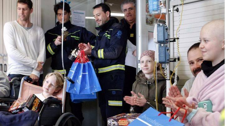 Los bomberos del Ayuntamiento entregan regalos a los niños ingresados en el hospital de La Paz