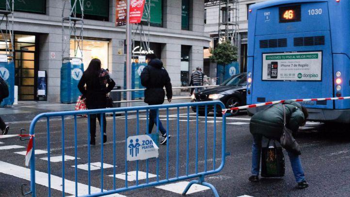 Peatones cruzan tras pasar una cinta de seguridad colocada en un cruce por el corte de la Gran Vía.