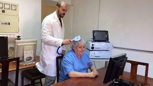 Ignacio Serrano, PhD e ingeniero del grupo G-nec del CSIC, realiza una Estimulación Magnética Transcraneal a una paciente.