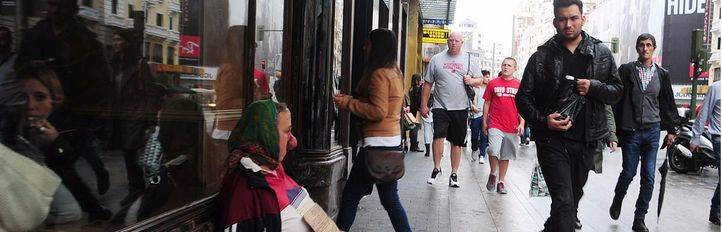 Una indigente (con una deformidad en la cara)  pide limosna en la Gran Vía